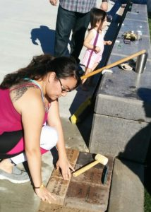 Photo of family member placing memorial brick